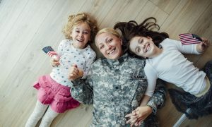 Military mom lays on the floor in their new home with her daughters