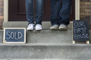Couple stands on porch of their newly purchased home with a Sierra Pacific Mortgage Home Loan